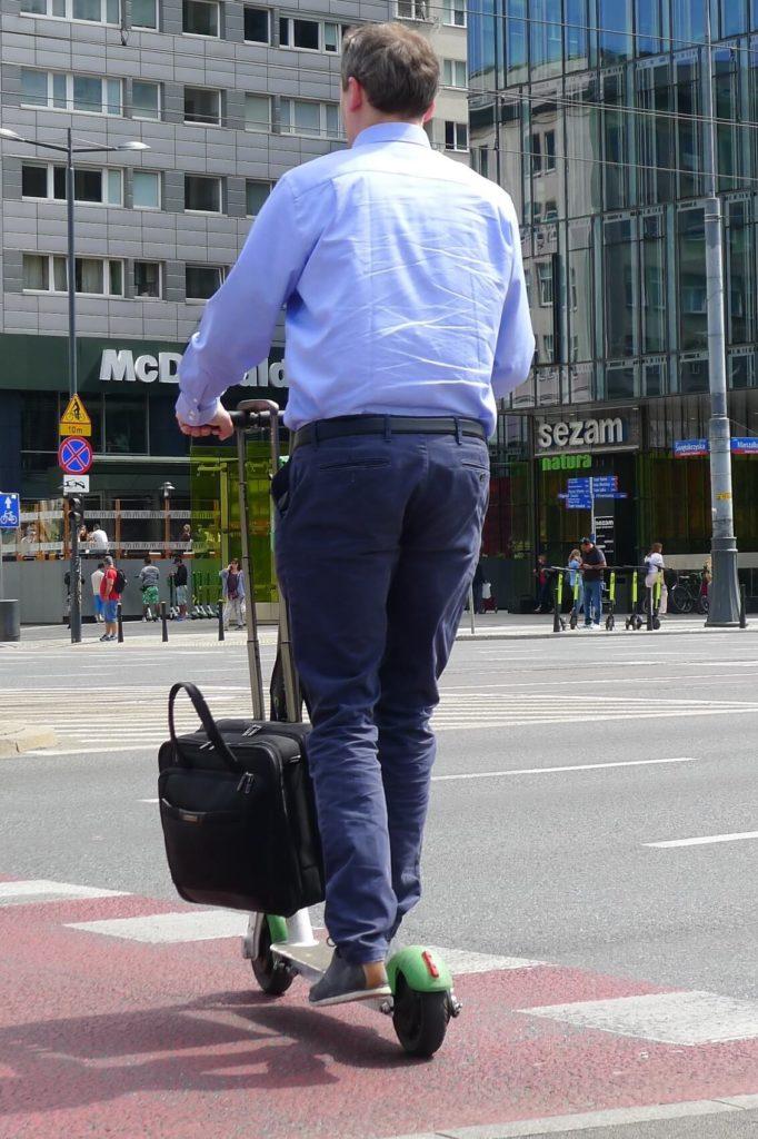 Hulajnogista z laptopem w Warszawie. UTO i mikromobilność